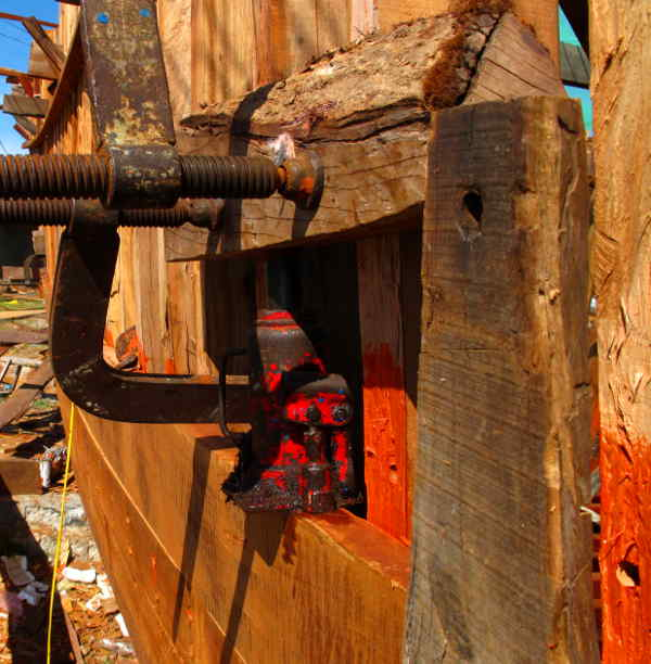 Clamps hold a piece of scrap planking to a pair of frames. Hydrualic jack sits on the plank that needs to move and the ram itself bears against the clamped off scrap wood.