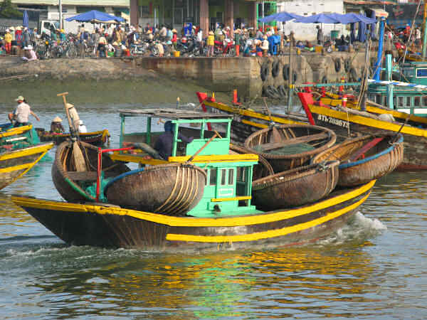 Basket Carrier in Phan Thiet. The round, woven bamboo boats have external, protective ribs.