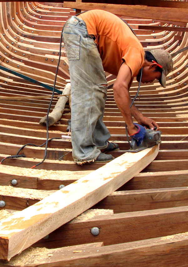 Boat builder sawing a timber