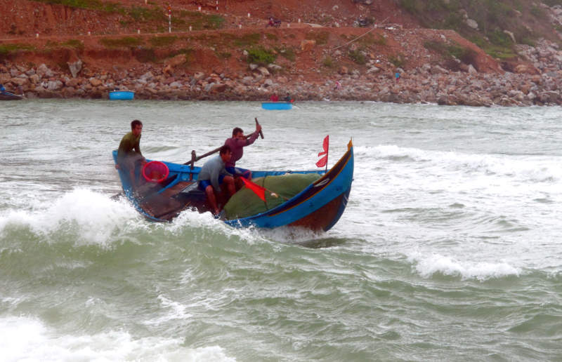 Composite woven bamboo & wood surf boat near Xuan Hai, approaching the beach through the surf.