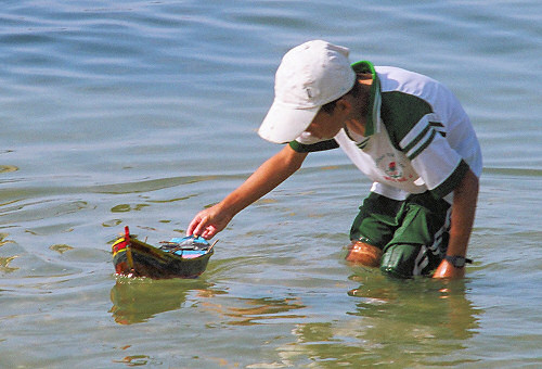Model Boat and boy in the water at Mui Ne beach.