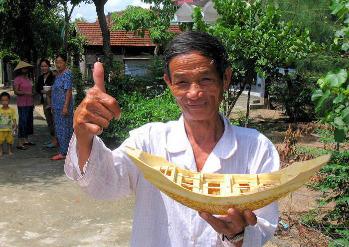 Man with small model woven basket boat, Thuan An